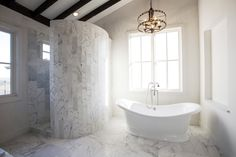 Spa-like Master Bathroom with marble tile and a beautiful slipper tub to soak away the daily stress.
