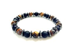 This mens beaded bracelet is made with 8mm matte black onyx beads and brown tiger eye beads, and accentuated by dark gray hematite rondelle beads. A cool, stylish look that matches any outfit easily. Good for layering with other bracelets and suitable for women too.  Sizing To choose the right size for your bracelet: 1. Use a measuring tape to measure your wrist size. If you do not have a measuring tape, you may use a string or strip of paper to go around your wrist, then measure the length…