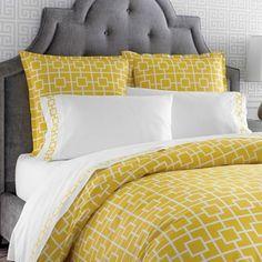 Jonathan Adler yellow bedding with gray headboard.