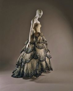 By 1949, Christian Dior's instinct for calibrated innovations of the body's 'line' had established him as fashion's preeminent arbiter. That year, dresses called 'Venus' and 'Junon' or Hera to the Greeks, were among the most coveted of his designs. Dior's Venus was realized in the delicate eighteenth-century grey that was his signature, frosted with iridescent beading and embroidery. But his Junon is more vividly conceived.   The magnificent skirt of ombrée (shaded) petals, like abstractions…