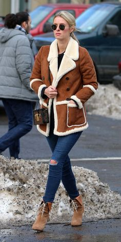 Nicky Hilton Rothschild wears a tabacco shearling coat, ripped blue jeans, Ray-Bans, and suede booties
