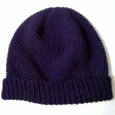 Knitted seed stitch hat with ribbed band.