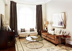 Blend warm neutrals for an easy, elegant look. The beauty of a coffeehouse-inspired color palette is that you can mix shades with abandon — in fact, the more the merrier. A warm cinnamon-brown sofa anchors this living room arrangement, supported by espresso drapes and pale latte-foam-colored walls.