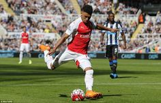 Arsenal winger Alex-Oxlade Chamberlain hits a shot at goal which is deflected into the net...