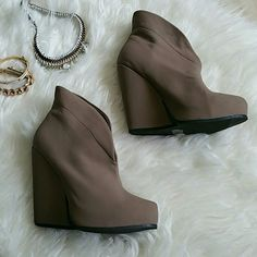 Taupe Wedge Booties Has a platform. There is visible scuffs and a black mrk on the inside part of the left shoe (2nd pic).  Man made materials. Qupid Shoes Ankle Boots & Booties