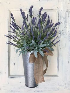 This farmhouse style lavender basket is the perfect accessory for your home, whether its used on the front door or as an accent piece for a powder room or guest room. A galvanized metal wall basket is filled with a beautiful mix of realistic faux lavender and sage. It is adorned with a