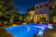 This modern patio features tropical landscaping around a cozy outdoor sitting area and a gorgeous pool illuminated with blue lighting.