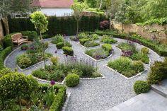 beau jardin contemporain en forme de cercle recouvert de gravier et avec des parterres de plantes vertes et fleurs