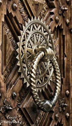 ornate door knocker on carved door