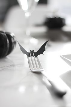 Paper bat in fork. Halloween table setting details.
