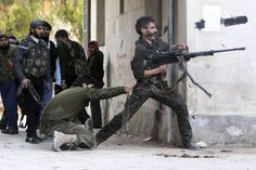 A Free Syrian Army fighter fired his weapon during clashes with forces loyal to Syrian President Bashar al-Assad in Aleppo Sunday. (Muzaffar Salman/Reuters)