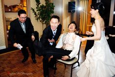 """This is another Korean wedding tradition: all the """"jealous"""" gentlemen bang the groom's feet and the bride had to dance for the gentlemen to stop it. - bayphoto.net"""