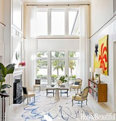 """A wild silk rug by Fort Street Studio and an Alexander Calder tapestry, Soleil Rouge, pull the eye down in the entry, """"so you don't notice that the ceiling is so high,"""" designer Robert Couturier says. Christophe Côme fireplace screen."""