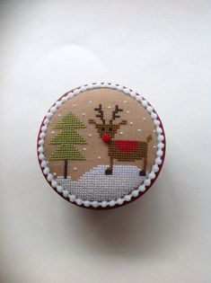 Gift giving is just around the corner! I have stitched a sweet little Christmas box with a reindeer and tree. This is adapted from a Lizzy Kate design. I have mounted a stitched piece on top of a paper mâché box that has been painted, distressed and waxed. It is cross stitched on a cocoa color linen with cotton threads. And trimmed in a tiny white Pom-Pom trim. The inside has also been finished with a quality holiday fabric. This piece measures approx. 2 1/2 inches high and 4 inches across…