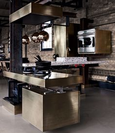 Gold metallic kitchen designed by Tom Dixon in collaboration with Lindholdt Studio. A flexible, beam hung modular system, combined with robust materials such as bronze, iron and stone.