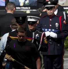 Firefighters present American flags, Arizona flags and pulaskis to family members of the fallen firefighters.