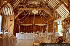Fairy light star canopy with central chandelier at Tewin Bury Farm Tithe Barn