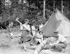 A member of the Auxiliary Territorial Service chops wood at a camp in Possingworth Park, Sussex, in May 1942 ~