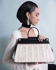 A model sitting on a chair is holding a Bellorita black and white hand tooled and hand painted leather satchel with calligraphy pattern.