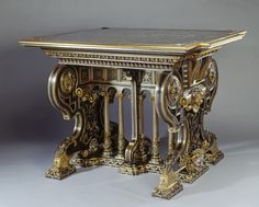 Located 2015 in the Grand Entrance & Marble Hall of Buckingham Palace, London, UK. Photo by unknown, made by Placido Zuloaga, of Center Table of metal covered with gold & silver with top of marble that is supported on scrolled end panels, carved with foliage & female & satyr heads. Ends rest on 3 pads, the center linked by a corinthian columns. Purchased by Queen Elizabeth (1900-2002) Scotland (wife of King George VI (1895-1952)) in 1938.