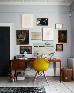 art wall, midcentury modern wood desk, gray paint, mustard eames eiffel chair, white wood floors, dark gray rug