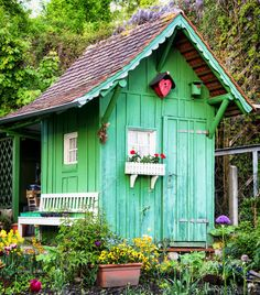 Painted a bright green, this ramshackle garden shed stands out against the surrounding planting beds. A small picket window box and a matching bench stand out against the bright green.