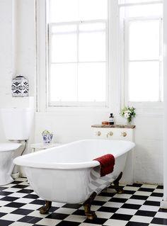 Black and white tiled flooring enlivens this white bathroom.