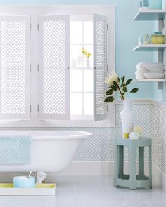 Choosing the right blue is all about creating a mood. Here, washes of light sky blue on the walls and lots of white evoke the tranquillity of a tropical breeze. A pale aqua on the underside of the shelves extends the theme for anyone who's in the tub. Add another tropical touch by using radiator-grill panels on the walls and as shutters to provide privacy without sacrificing light. Coordinated accessories -- a table, glass canisters -- plus items in a contrasting sunny citrus enhance the…
