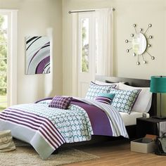 Halo brings youth and vibrancy to your bedroom with a teal and white checkered print and horizontal purple stripes. A gray stripe runs along the bottom of the comforter. The reverse is covered in a more subtle gray and white striped print. Made from polyester this comforter is machine washable for easy care. Includes two decorative teal and white pillows.