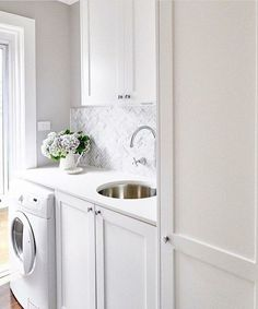 gray laundry rooms Small white laundry room features a front loading washer enclosed beside white shaker cabinets fitted with polished nickel knobs and a white quartz countertop fitt Laundry Room Inspiration, Room Design, Laundry Mud Room, Metal Sink, Herringbone Backsplash, White Laundry Rooms, White Shaker Cabinets, Small Laundry Room, White Laundry