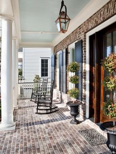 masonry, wood color, black shutters, white columns, brick porch    Quinlan Residence