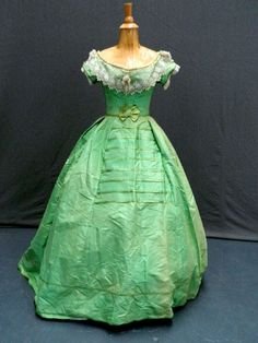 A stunning apple green mid 19th Century silk dress comprising a skirt, bodice, jacket and waist belt. The bodice is trimmed with cream lace and bead detail. The jacket has silk thread covered buttons. Theodore Bruce
