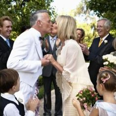 A mature bride and groom kiss during a wedding ceremony.