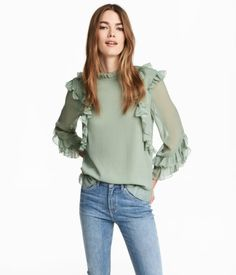 Dusky green. Straight-cut blouse in double-layer crinkled chiffon with a small ruffled collar and decorative ruffles at top, cuffs, and hem. Opening at back