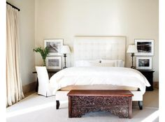 The master suite features an oversize custom upholstered headboard that's flanked by black-and-white photography. The duvet was created from a white-on-cream Oaxacan textile, and the carved bench was found during a shopping trip to San Miguel de Allende. The carpet is from Mendel Tencer.