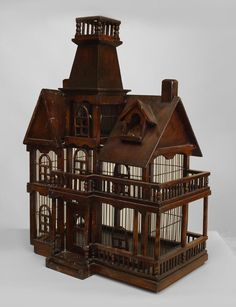 English Victorian style stained wood birdcage in the form of a house with a center widow's walk and gables with a balcony and porch