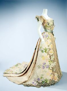 Silk evening dress, 1902, House of Worth. This beautiful example of a Belle Époque dress emphasizes the aesthetic of pastel colors & light materials. The cutout work of the chiné applied to the lace makes the flowers appear to grow. Chiné is expensive to make as the pattern is printed on the warp before the weft is woven in, producing a blurred effect reminiscent of a Claude Monet painting.