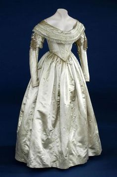 """ca 1840 """"old gold"""" colored silk satin wedding dress with ornate ornamentation on sleeves (see close up picture). Also came with a short cape with an edging of white swan's down. England."""