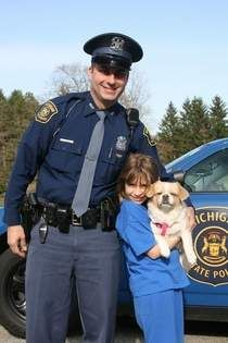 TROOPER REUNITES GIRL WITH DOG - Lindsey Hamm and her dog, Diva, with their hero, Michigan State PoliceTrooper Randy Gariglio. Diva disappeared Sunday night from her home near Ionia High School, and was found by Gariglio Monday morning near the MSP post on Riverside Drive.