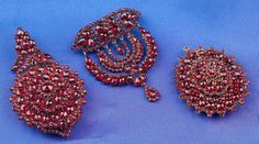Three Antique Garnet Jewelry Items, two pendant lockets and a flexible swag brooch, pave-set with fancy-cut garnets, gilt mounts, lg. 2 5/8, 1 5/8, 2 in.