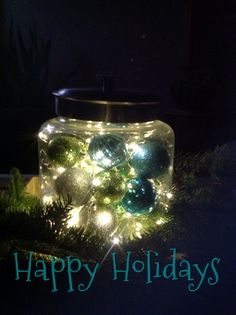 Modern Christmas decor.  battery operated mini lights with favorite colored orna,ents in a cookie jar atop,a bed of fresh greenery