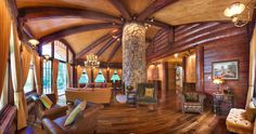 Wide angle view of a great room in a Catskills log home. I kept the interior log walls slabbed flat and added a couple of carved curved walls to mirror the fireplace. I had the log rafters radiate off an oval-shaped fireplace.  #logcabin #loghome #postandbeam #postandbeamdesign