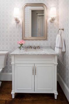 White and gray powder room features walls clad in gray geometric wallpaper lined with a white single washstand topped with carrera marble placed under a silver leaf beaded mirror illuminated by Worlds Away Delilah Silver Wall Sconces.