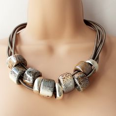 Gorgeous chunky Greek ceramic beads with a fabulous snakeskin finish combined with silver rings onto a multi-strand silk wrapped cords Muted tones of