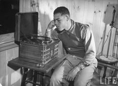 Heavyweight boxing champion Joe Louis listening to a Victrola, 1940