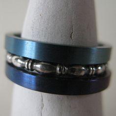 Heidi Janssen. Set ringen van titanium en zilver. een setje ringetjes van titanium, deze keer in verlopende tinten blauw, gecombineerd met een fantasieringetje in geoxideerd zilver.