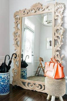Chic foyer features a Restoration Hardware Rococo Leaner Mirror and a blue umbrella holder alongside a a leopard rug.
