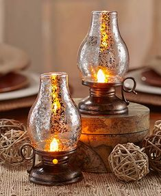Add a classic country look to your home decor with this Set of 2 Lighted Hurricane Lanterns. Each lantern has a mercury glass look and a realistic amber-colored