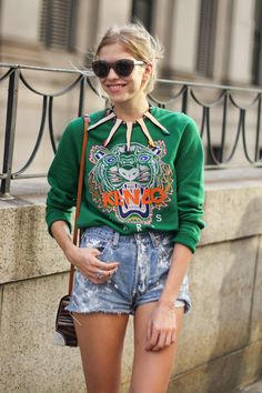 Green KENZO sweatshirt with classic distressed jean cutoffs. Love the leg necklace too!