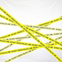 Composition: Line. Line is the straight edges of yellow police caution tape that continue down the background in a straight, mechanical manner.